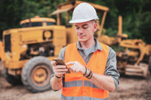 Worker with construction equipment managing it on his phone
