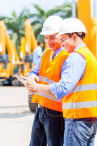 Workers consult a mobile tablet in an equipment yard